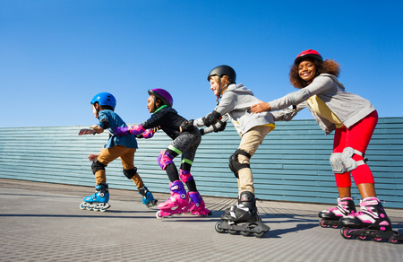 Kids in safety helmets rollerblading on the track