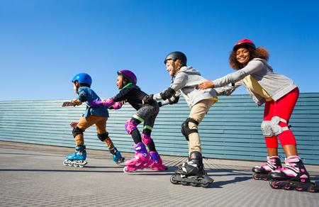 Kinderen in veiligheidshelmen skaten op de baan