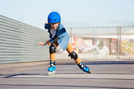 야외 스케이트 공원에서 롤러 스케이트 타고있는 소년