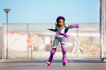 African girl rollerblading fast at skate park Stock Photo