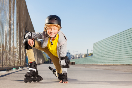 Smiling boy with inline skates and protective gear
