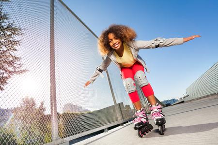 Chica africana activa patinar en el parque de patinaje