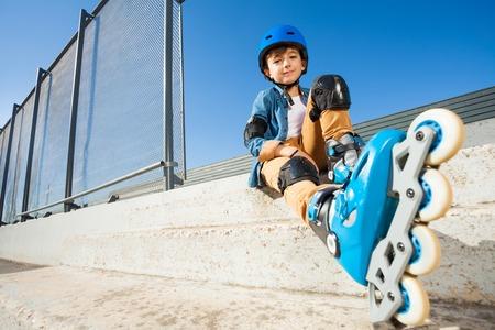 Roller boy resting on the steps of skate park