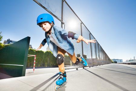 Chłopiec w rolkowych ostrzach robi sztuczkom przy łyżwowym parkiem