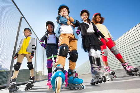 Boy in rollerblades standing with friends outdoors Foto de archivo