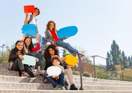 Cute teenage boys and girls holding speech bubbles Stock Photo
