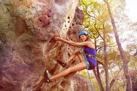 Woman rock climbing with harness in forest area