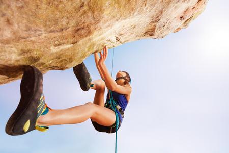 Rock climber training outdoors against blue sky Standard-Bild