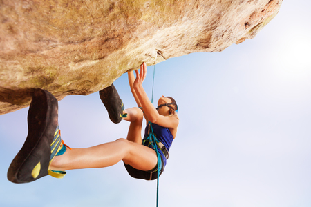 Rock climber training outdoors against blue sky Stockfoto