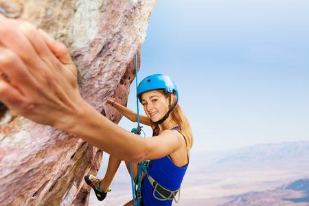 Sporty young woman in helmet rock climbing Imagens - 93312365