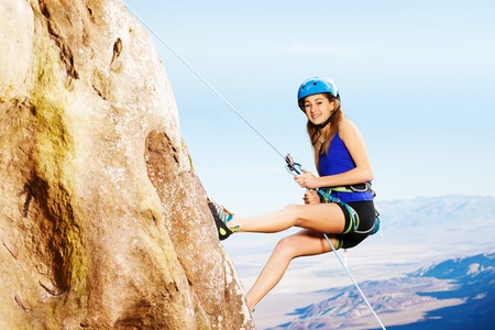 Side view portrait of female climber using technique of the abseil method of roping down