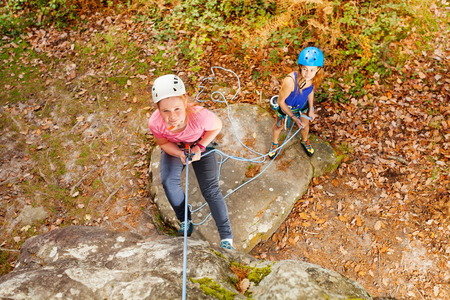 Top view portrait of teenage girl in helmet abseiling training on steep rock with female instructor in forest area