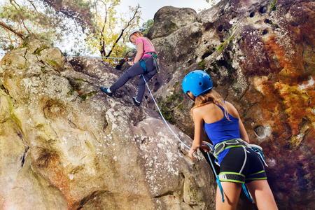 Female rock climbing instructor helping teenage girl to reach the summit of the mountain