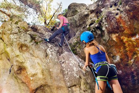 Istruttore femminile di arrampicata su roccia che aiuta l'adolescente a raggiungere la cima della montagna Archivio Fotografico - 93312368