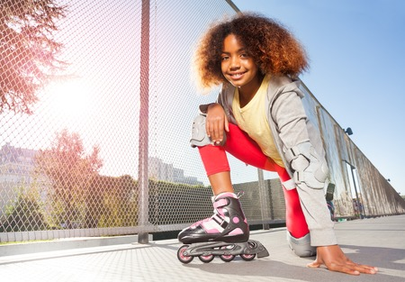 Happy African girl posing on floor at skate park