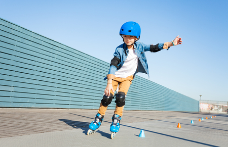 Boy learning to roller skate on road with cones