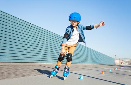 Chłopiec uczy się jeździć na rolkach na drodze ze stożkami Zdjęcie Seryjne