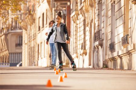 Teenage girl roller skating at city side walk Stock Photo