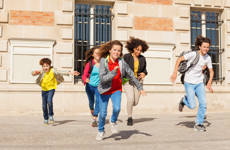 Cute pupils running  from school building Banco de Imagens