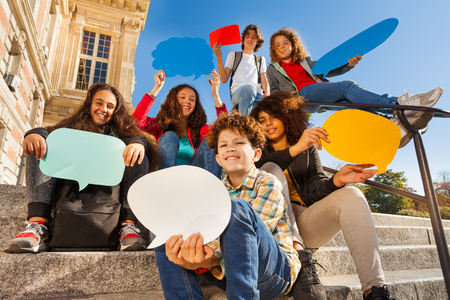 Smiling teenage boys and girls with speech bubbles