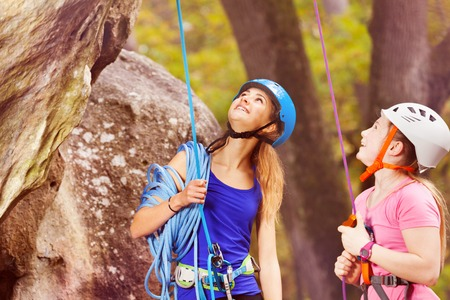 Rock climbing trainer with teenage girl looking up Stock Photo