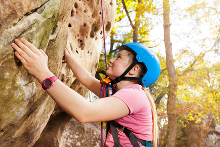 Teenage rock climber exercising outdoors in forest