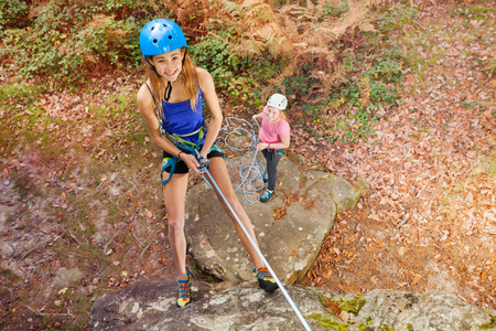 Instructor teaching teenager to abseil outdoors