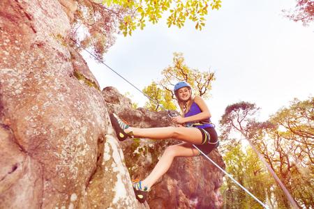 急な岩の上で訓練を受けている若い女性