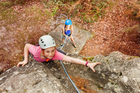 Girl training rock climbing in forest area