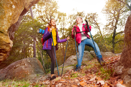 Happy travelers with backpacks walk along a trail