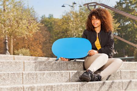 Teenage girl holding blue empty speech bubble Stock Photo