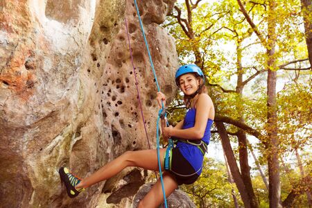 Happy woman rock climbing in forest area Stok Fotoğraf