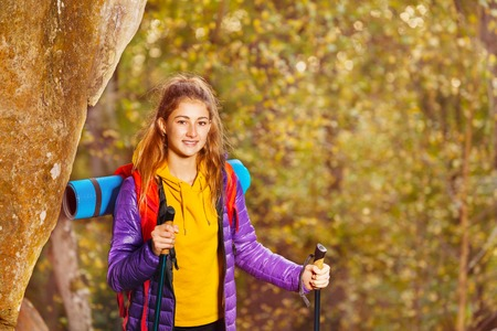 Beautiful hiker with trekking poles and backpack