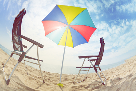 Deck chairs under sun umbrella on the sandy beach Stock Photo