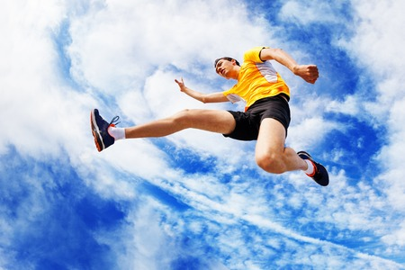 Sportsman remains in air while jumping against sky