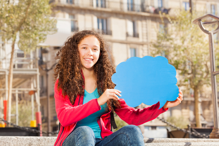 Cute teenage girl sitting on the stairs outdoors, holding blanked speech cloud