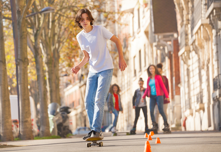 Portrait of teenage boy skateboarding around the cones at city side walk Stock Photo