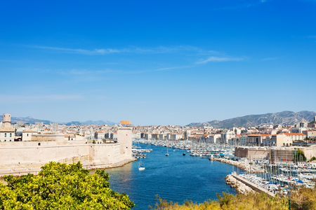 Beautiful picture of Mediterranean coastline with Fort Saint-Jean to the left and Marseille cityscape to the right at sunny day