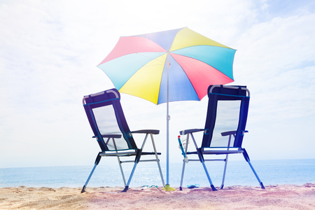Two chairs and opened multicolored sun umbrella on the beach in summer 写真素材