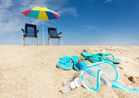 Two pairs of step ins and blue snorkeling mask with snorkel laying on sandy shore in summer