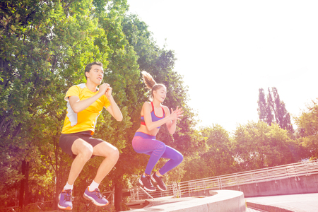 Active people doing box jump exercise during crossfit workout outdoors in summer Archivio Fotografico - 106037390