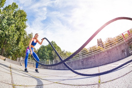 Female athlete making wave movement with battle rope during crossfit workout at outdoor stadium at sunny day