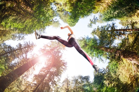 Sporty girl running in sunny forest Stock Photo