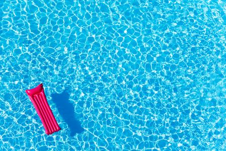 Roze opblaasbare matras drijvend op het wateroppervlak Stockfoto