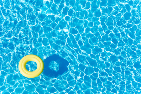 Empty rubber ring floating on blue water surface