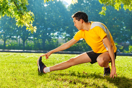 Elastyczny młody człowiek rozciągający nogi na zewnątrz Zdjęcie Seryjne