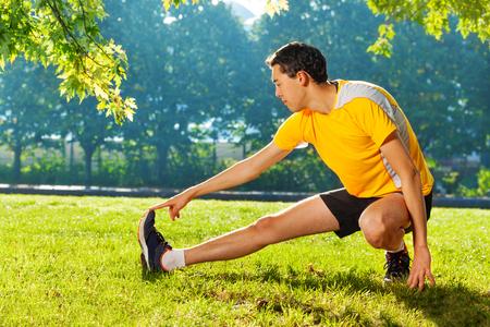 Flexibele jonge man die zich uitstrekt benen buitenshuis Stockfoto