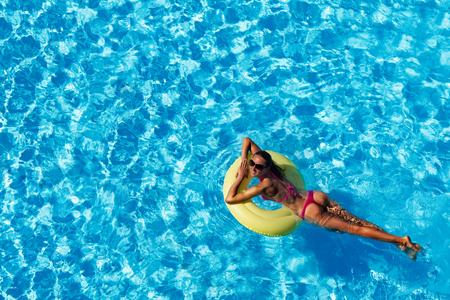 femme souriante nager sur anneau en caoutchouc dans la piscine