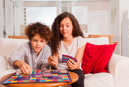 Happy teens playing table game together at home Standard-Bild