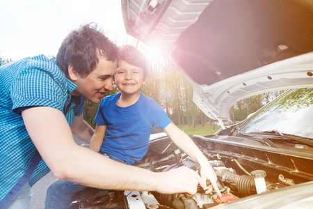 Young father teaching his little son repairing car Foto de archivo